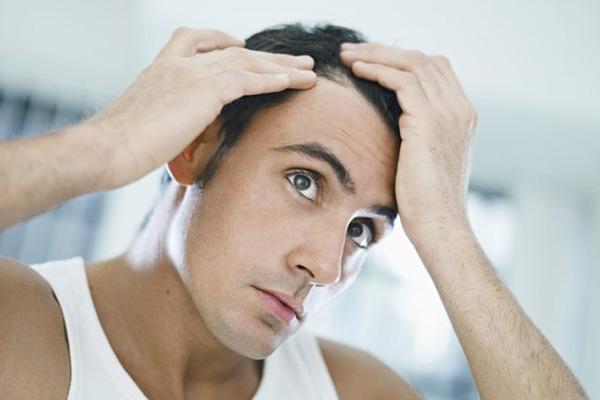 mężczyzna sprawdza swoje włosy na głowie