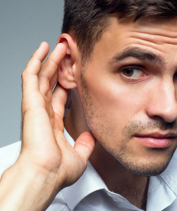 mężczyzna pokazuje, że słucha